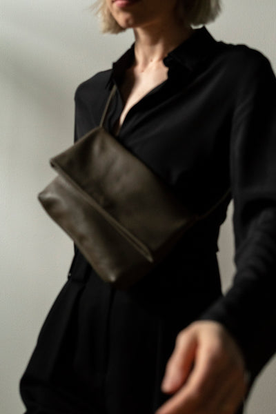 female model walking with a taupe leather crossbody bag