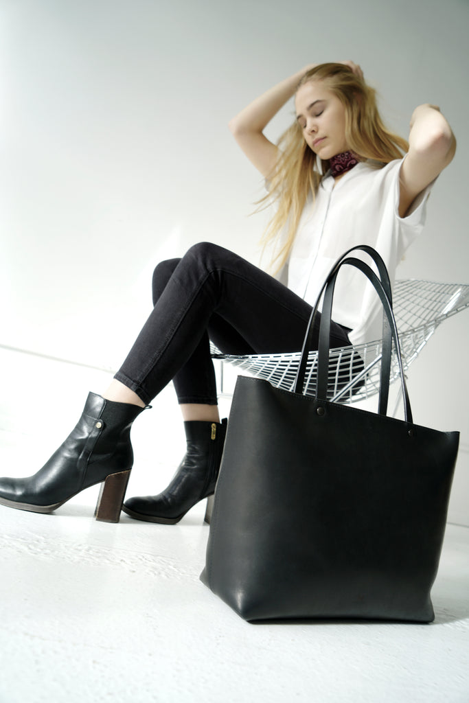 Female model sits next to large black leather tote