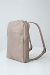 male model wearing the dusk backpack in taupe leather