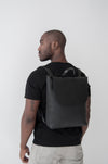 front view of the large ray backpack in black pebbled leather with a veg tan flap