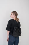 female model wearing small aura backpack in beige Horween dearborn leather