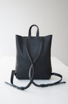 The front view of the Small Ray Backpack in black pebbled leather with veg tan flap