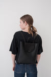 Female model wearing the Small Ray Backpack in black pebbled leather with veg tan flap