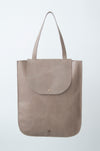 female model wearing the dawn oversized tote in taupe leather