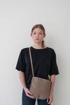 female model wearing the emit crossbody in taupe leather