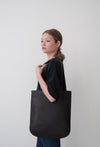 female model wearing the emit tote in black Horween essex veg tan leather