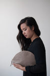 female model holding the halo clutch in taupe leather