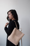 Female model with the Small Ray Backpack in Horween beige dearborn leather