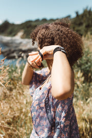 Girl putting on Kooshoo black hair ties. Available for purchase on The Conservationist.