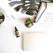 Stylized image of Breathe Deeply aromatherapy mist sitting on a desk. Available for purchase on The Conservationist.