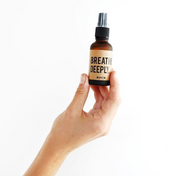 A person's hand holding the Breathe Deeply Mini. This shows the smaller size of the aromatherapy mist. Available for purchase on The Conservationist.