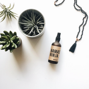 Image of Namaste Ninja Aromatherapy Mist on a white table with succulents. Brown fogged glass with kraft paper label. Available for purchase on The Conservationist.