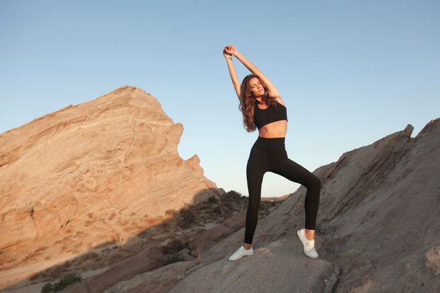 The Conservationist: Eco-friendly black leggings made out of post consumer recycled plastic. Lifestyle shot of woman on mountain wearing leggings.