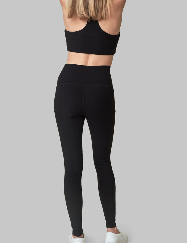 The Conservationist: Eco-friendly black leggings made out of post consumer recycled plastic. Back facing image of  black leggings.