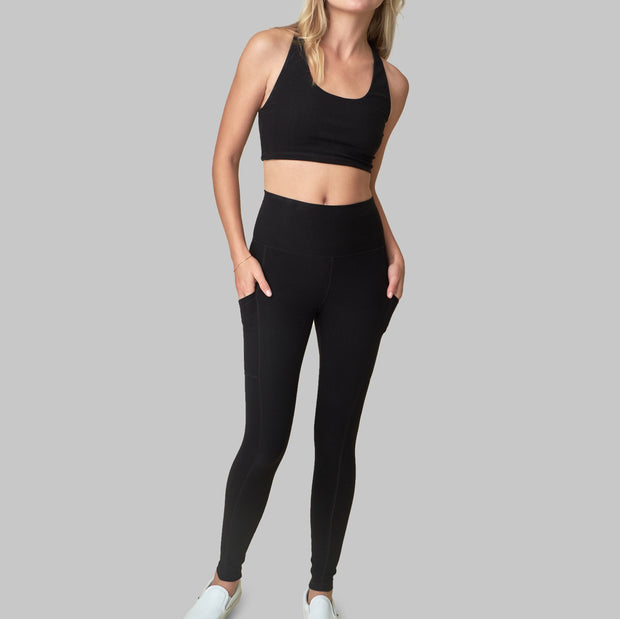 The Conservationist: Eco-friendly black leggings made out of post consumer recycled plastic. Front facing image of  black leggings with hands in deep side pocket.