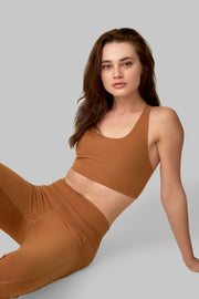 Front facing image of a rich turmeric colored eco-friendly yoga exercise top, made from post consumer recycled plastic. Available on The Conservationist.