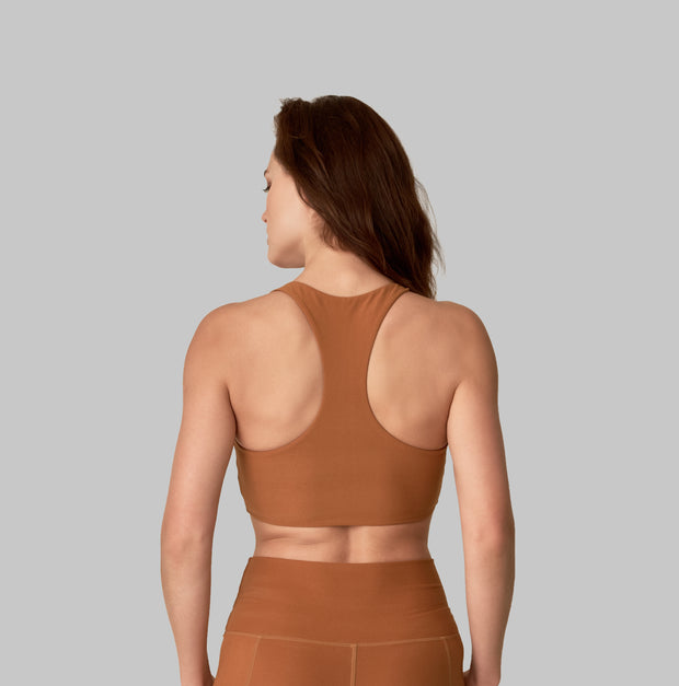 Back facing image of a rich turmeric colored eco-friendly yoga exercise top, made from post consumer recycled plastic. Available on The Conservationist.