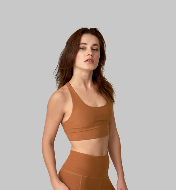 Side facing image of a rich turmeric colored eco-friendly yoga exercise top, made from post consumer recycled plastic. Available on The Conservationist.