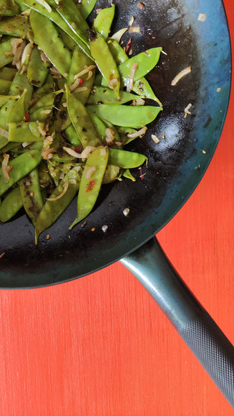 Close up of a carbon steel wok on a red background. Inside the wok is a stir fry of snow peas, shallots, garlic and chilis.