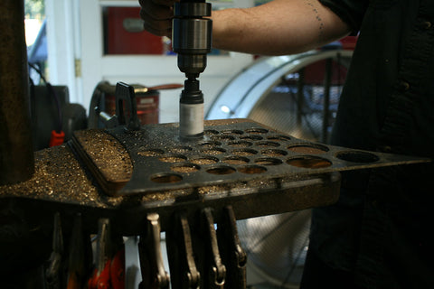 a close up picture of a drill press hole saw being used by Cory to cute brass elements for the woks inside the Studio Weyh work shop