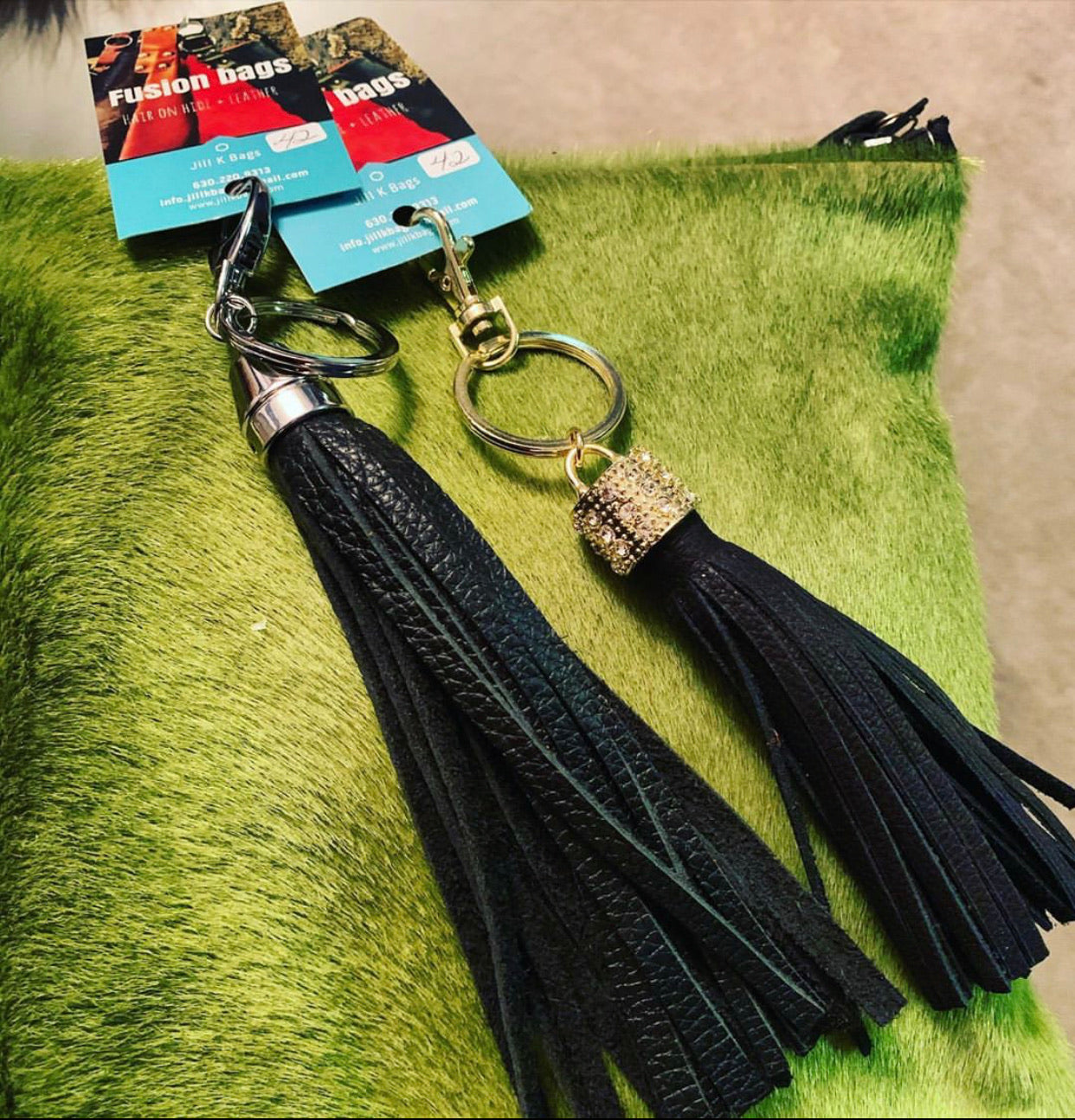 Green hair on hide fused to black leather clutches/zipper pouch with black tassel