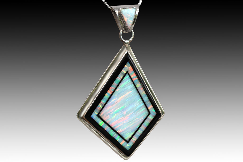280L - LARGE WHITE FIRE OPAL PENDANT INLAID WITH BLACK STONES