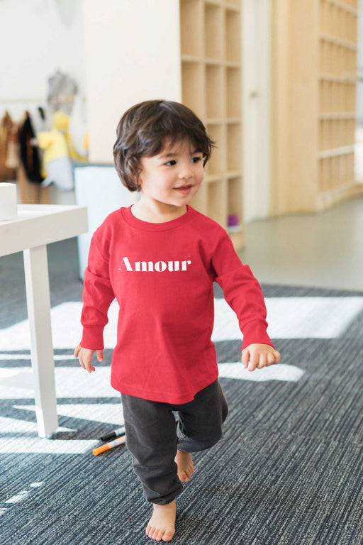 child smiling and wearing red amour long sleeve toddler shirt
