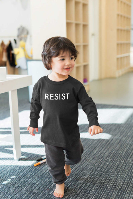 child wearing black resist long sleeve shirt walking at the nook