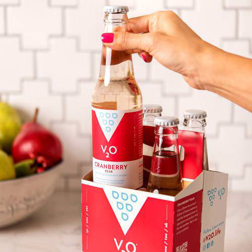 person grabbing cranberry pear v2o by a fruit bowl