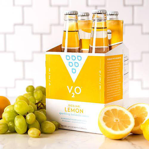 sicilian lemon v2o surrounded by grapes and lemons