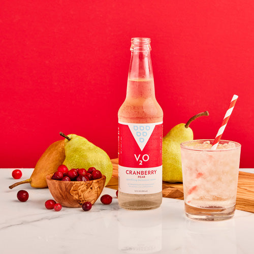 Bottle of V2O Cranberry Pear surrounded by fruit with red backdrop