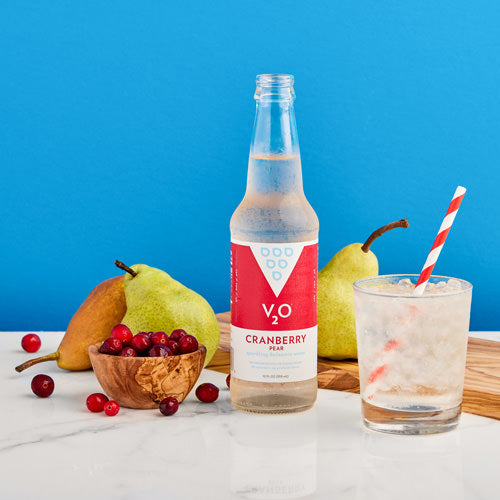 Bottle of V2O Craberry Pear surrounded by fruit with blue backdrop
