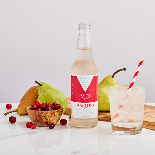Glass and bottle of Cranberry Pear V2O surrounded by fruit