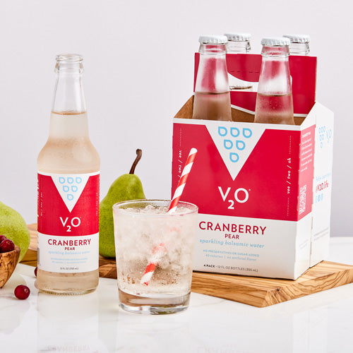 Bottle, 4-pack and glass of V2O Cranberry Pear surrounded by fruit