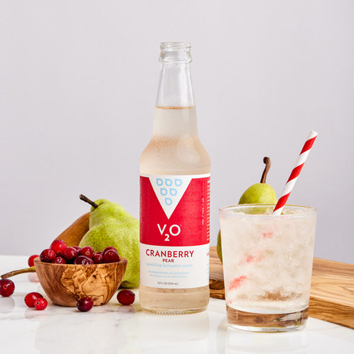 Glass of V2O Cranberry Pear surrounded by fruit