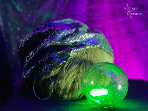A fortune teller Tribble, wearing a spiderweb headdress and staring into a glowing crystal ball
