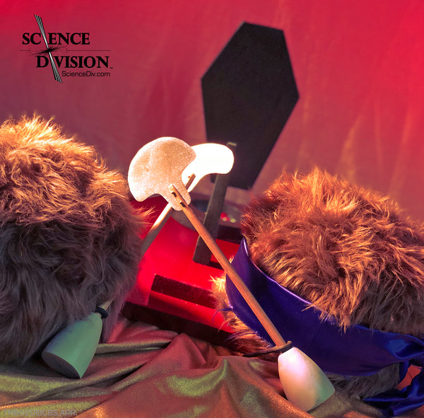 Two Tribbles, one in a purple sash, battling each other on a re-created of the Amok Time set