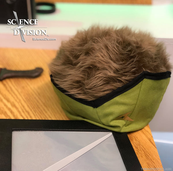 A Tribble in Kirk's green wraparound uniform with the TOS version of a PADD
