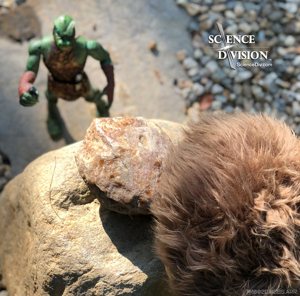 A Tribble on top of a tall rock, ready to push a boulder down onto an action figure Gorn