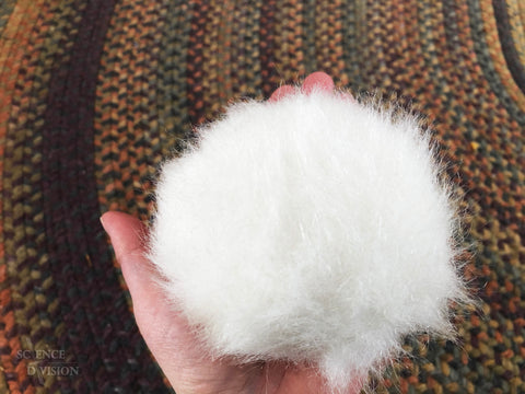 A hand holding a small white Tribble about the same size as the hand