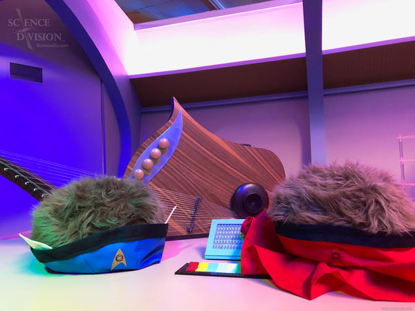 Tribbles dressed as Spock and Uhura in front of a Vulcan lute