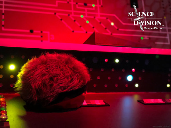 A Tribble dressed as Scotty in front of an Engineering panel