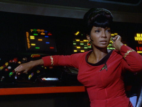 Lt. Uhura with her hand to her earpiece
