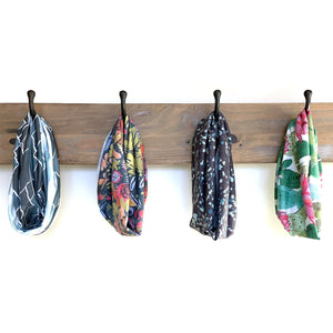 different colored SHREDLY beck gaiters, buffs, hanging from wall hooks