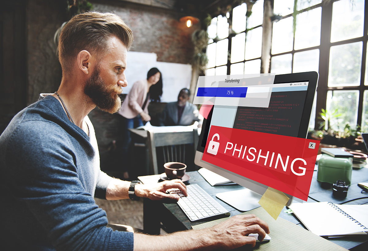 Cyber criminal on computer phising which shows the importance of educating your team on cyber attack prevention.