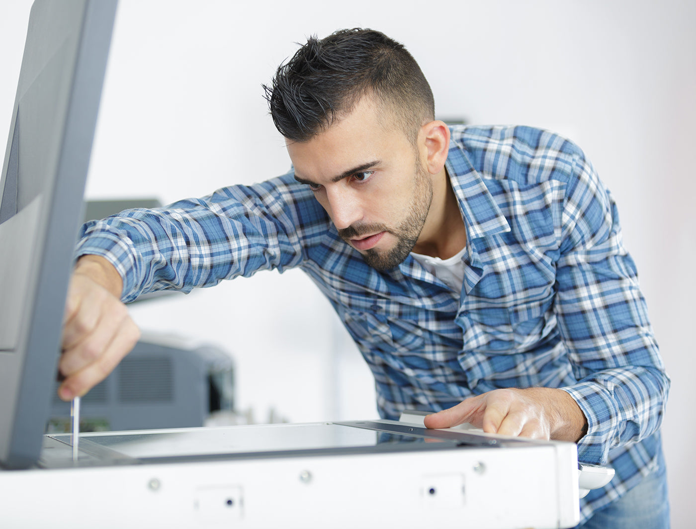 Service technician mending office photocopier