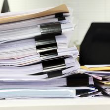 Tall stack of papers on desk