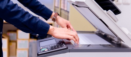 Young man's hands scanning document at copier