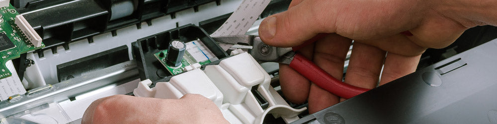 Image showcasing a man performing maintenance on an office printer
