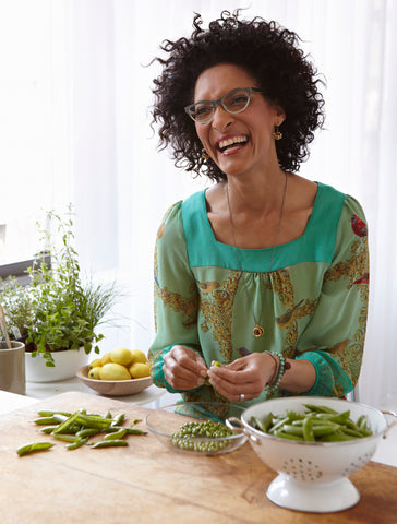 Carla shelling peas while wearing glasses